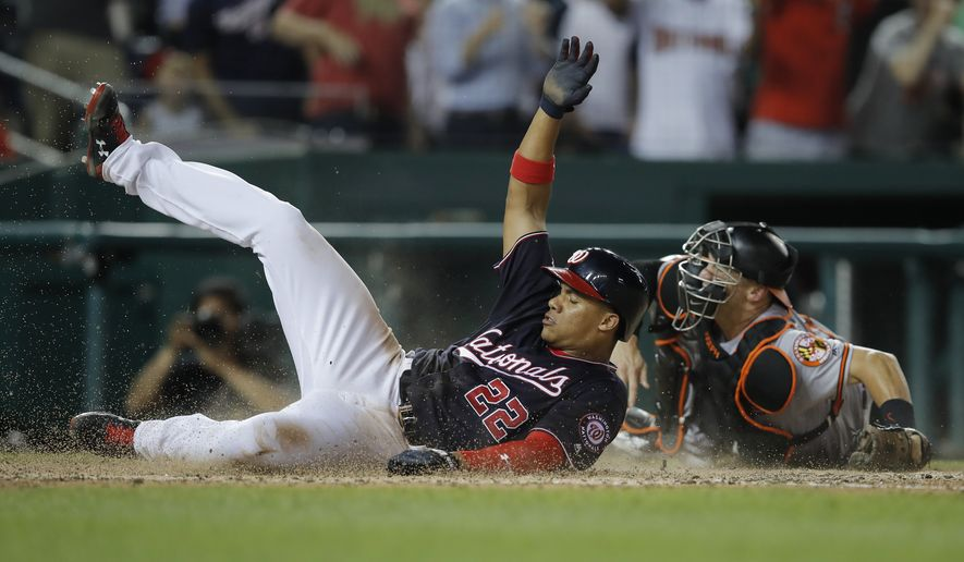 Washington Nationals' Juan Soto slides into home past Baltimore Orioles catcher Caleb Joseph to score on a double by Anthony Rendon during the seventh inning of a baseball game at Nationals Park, Tuesday, June 19, 2018, in Washington. The Nationals won 9-7. (AP Photo/Carolyn Kaster)