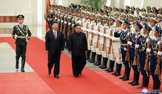 "In this June 19, 2018, photo provided on June 20, 2018, by the North Korean government, Chinese President Xi Jinping, center left, and North Korean leader Kim Jong Un, center right, inspect the honor guard at the Great Hall of the People in Beijing, China. Korean language watermark on image as provided by source reads: ""KCNA"" which is the abbreviation for Korean Central News Agency. (Korean Central News Agency/Korea News Service via AP)"
