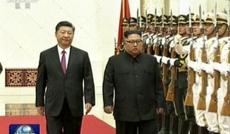 In this image taken from a video footage run by China's CCTV on June 19, 2018, via AP Video, Chinese President Xi Jinping, left, walks with North Korean leader Kim Jong Un during a welcome ceremony at the Great Hall of the People in Beijing. (CCTV via AP Video)