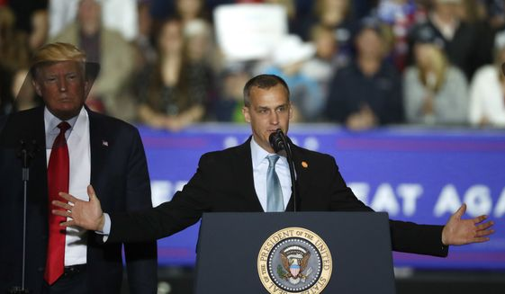 """FILE - In this April 28, 2018 file photo, President Donald Trump, left, watches as Corey Lewandowski, right, his former campaign manager for Trump's presidential campaign, speaks during a campaign rally in Washington Township, Mich. Lewandowski has created a stir by dismissing a story about a girl with Down syndrome with a sarcastic """"Wah wah."""" Lewandowski appeared Tuesday, June 19, 2018, on Fox News Channel to discuss the president's hard-line immigration policy, which has led to the practice of taking migrant children from parents charged with entering the country illegally. (AP Photo/Paul Sancya, File)"""