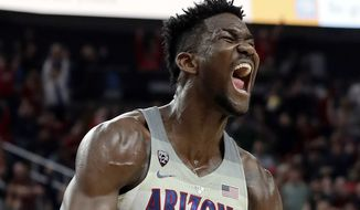 FILE - In this March 10, 2018, file photo, Arizona's Deandre Ayton reacts after a dunk against Southern California during the second half of an NCAA college basketball game for the Pac-12 men's tournament championship, in Las Vegas. Ayton was a force in his lone college season and looks like the favorite to land with Phoenix as the No. 1 overall pick in Thursday's NBA Draft. (AP Photo/Isaac Brekken, File) **FILE**