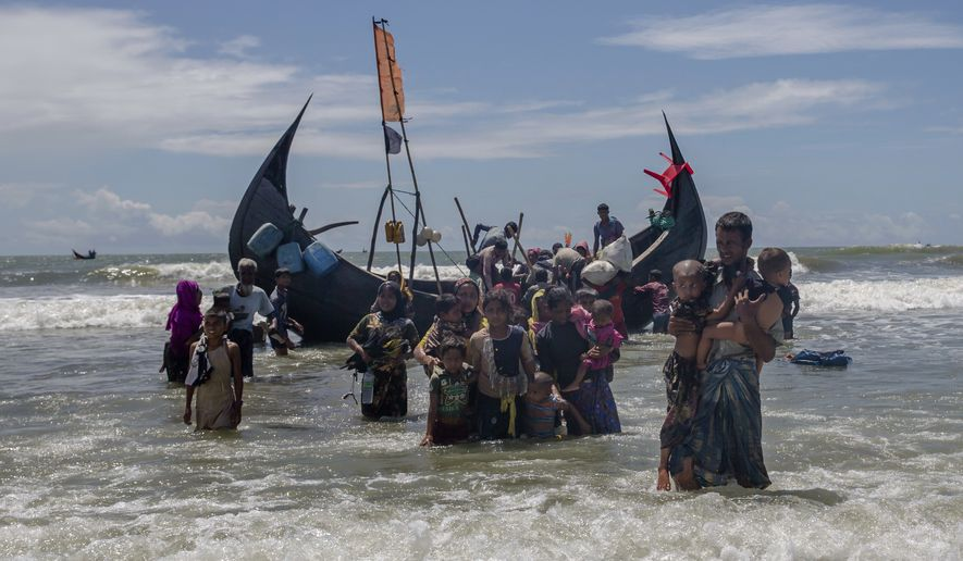 In this Sept. 14, 2017, file photo, a Rohingya man carries two children to shore in Shah Porir Dwip, Bangladesh, after they arrived on a boat from Myanmar. The U.N. refugee agency says nearly 69 million people who have fled war, violence and persecution were forcibly displaced last year, a new record for the fifth straight year. The U.N. High Commissioner for Refugees said Tuesday, June 19, 2018 that continued crises in places like South Sudan and Congo, as well as the exodus of Muslim Rohingya from Myanmar starting last year, raised the overall figure of forced displacements in 2017 to 68.5 million. (AP Photo/Dar Yasin, File)