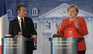 France's President Emmanuel Macron listens to German Chancellor Angela Merkel, right, at a press conference after a meeting in the guest house of the German government in Meseberg north of Berlin, Germany, Tuesday, June 19, 2018. (AP Photo/Jens Meyer)