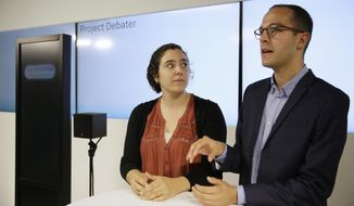 Noa Ovadia, left, and Dan Zafrir, right, prepare for their debate against the IBM Project Debater, Monday, June 18, 2018, in San Francisco. IBM on Monday will pit a computer against two human debaters in the first public demonstration of artificial intelligence technology it's been working on for more than five years. The system, called Project Debater, is designed to be able to listen to an argument, then respond in a natural-sounding way, after pulling in evidence it collects from Wikipedia, journals, newspapers and other sources to make its point. (AP Photo/Eric Risberg)