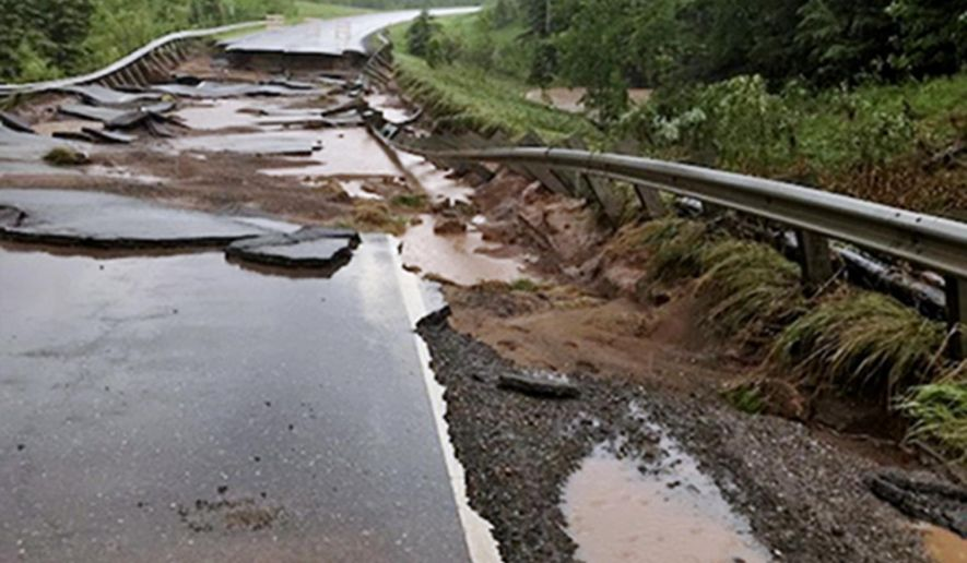 This Sunday, June 17, 2018, photo provided by the Minnesota Department of transportation shows Minnesota Highway 23 damaged by flash flooding at the south fork Nemadji River crossing near Wrenshall, Minn. The National Weather Service has since extended a flood warning through Thursday for northwestern Wisconsin and neighboring areas in Minnesota. (Chris Cheney/Minnesota Department of Transportation via AP)