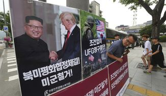 "A photo showing U.S. President Donald Trump and North Korean leader Kim Jong-un is displayed as a member of People's Democratic Party stands to oppose military exercises between the United States and South Korea near the U.S. embassy in Seoul, South Korea, Tuesday, June 19, 2018. The Pentagon on Monday, June 18, 2018, formally suspended a major military exercise planned for August with South Korea, a much-anticipated move stemming from Trump's nuclear summit with Kim. The signs read: "" Stop Ulchi Freedom Guardian (UFG) exercises and withdrawal of U.S. troops."" (AP Photo/Ahn Young-joon)"