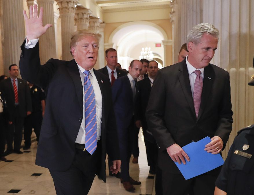 President Donald Trump, left, gestures as he walks with House Majority Leader Kevin McCarthy of Calif., right, while leaving the U.S. Capitol in Washington after meeting with GOP leadership, Tuesday, June 19, 2018. Walking behind them is Stephen Miller, center, White House senior adviser. (AP Photo/Pablo Martinez Monsivais)