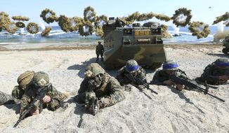 In this March 12, 2016, file photo, Marines of the U.S., left, and South Korea wearing blue headbands on their helmets, take positions after landing on a beach during the joint military combined amphibious exercise, called Ssangyong, part of the Key Resolve and Foal Eagle military exercises, in Pohang, South Korea. (Kim Jun-bum/Yonhap via AP, File)