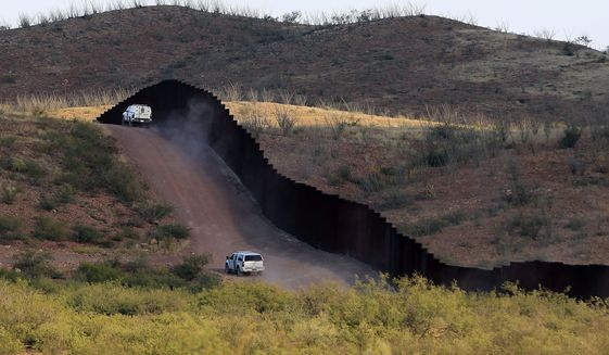 In this Oct. 2, 2012, file photo, U.S. Border Patrol agents patrol the border fence in Naco, Ariz. (AP Photo/Ross D. Franklin, file)