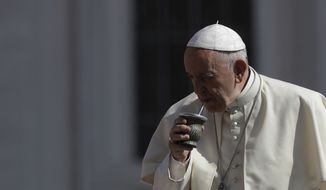Pope Francis drinks some mate offered by a pilgrim as he arrives in St. Peter's Square at the Vatican, for his weekly general audience, Wednesday, June 20, 2018. (AP Photo/Alessandra Tarantino)