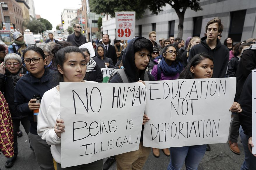 In this Feb. 28, 2018, file photo, demonstrators hold signs outside of the Immigration and Customs Enforcement offices in San Francisco. (AP Photo/Marcio Jose Sanchez, file)
