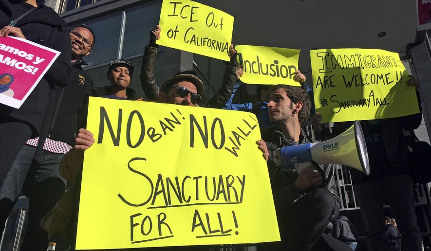 In this April 14, 2017, photo, protesters hold up signs outside a courthouse where a federal judge was to hear arguments in the first lawsuit challenging President Donald Trump's executive order to withhold funding from communities that limit cooperation with immigration authorities in San Francisco. After repeatedly suing the Trump administration over U.S. immigration policies, California will find itself in an unusual position Wednesday, June 20, 2018: defending protections for people in the country illegally against a court challenge by the federal government. U.S. Judge John Mendez in Sacramento will hear arguments from attorneys for the state and the U.S. Justice Department about a federal request to block three California laws. (AP Photo/Haven Daley) **FILE**