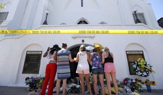 """FILE - In this June 18, 2015, file photo, a group of women pray together at a makeshift memorial on the sidewalk in front of the Emanuel AME Church, in Charleston, S.C.  A judge dismissed a lawsuit, June 18, 2018, against the FBI for a faulty background check that allowed Dylann Roof to buy the gun he used to kill nine people in a racist attack at a South Carolina church.  U.S. District Judge Richard Gergel also blasted the federal government's """"abysmally poor policy choices"""" in running the database for firearm background checks.  (AP Photo/Stephen B. Morton, File)"""