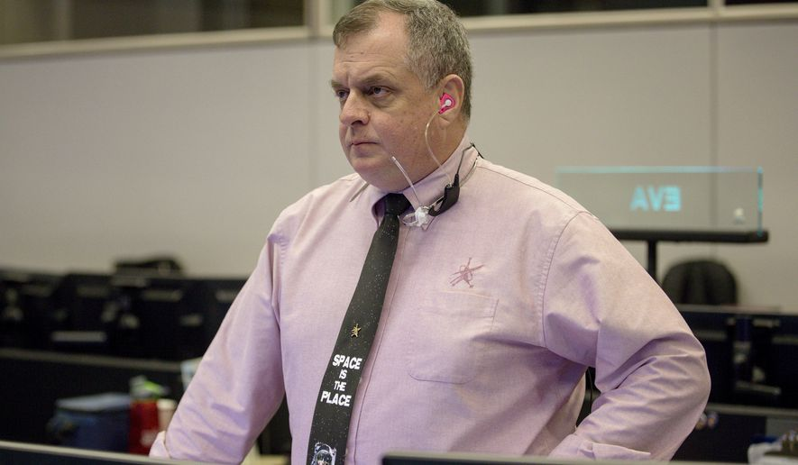 """In a Friday, April 27, 2018 photo, Timothy """"T.J."""" Creamer, right, a former astronaut and current mission control flight director at NASA, works in the mission control room at the Johnson Space Center, in Houston. ( Jon Shapley/Houston Chronicle via AP)"""