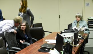 FILE - In this May 4, 2018, file photo, defendant Louise Anna Turpin, second left, talks with an investigator as her husband David Allen Turpin, right, looks on during a court appearance in Riverside, Calif. David and Louise Turpin are scheduled to appear for a preliminary hearing on Wednesday, June 20, 2018, in Riverside County Superior Court. A judge is set to hear testimony from law enforcement officers and consider whether authorities have amassed sufficient evidence for the Turpins to stand trial. They've pleaded not guilty to torture, child abuse and other charges. (Watchara Phomicinda/The Press-Enterprise via AP, Pool)