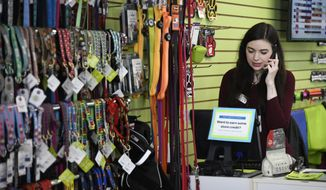 Caitlin Swedroe talks to a customer over the phone at Two Bostons Pet Boutique, Wednesday, June 20, 2018, in Naperville, Ill. Swedroe, 29, is a manager at the store. (AP Photo/Annie Rice)