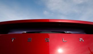 In this April 15, 2018, file photo, the sun shines off the rear deck of a roadster on a Tesla dealer's lot in the south Denver suburb of Littleton, Colo. (AP Photo/David Zalubowski, File)
