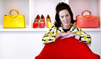 FILE - In this May 13, 2004 file photo, the late designer Kate Spade poses with handbags and shoes from her next collection in New York. The funeral  for Spade will be held on Thursday, June 21, 2018 at Our Lady of Perpetual Help Redemptorist Church in Kansas City, Mo. (AP Photo/Bebeto Matthews, File)