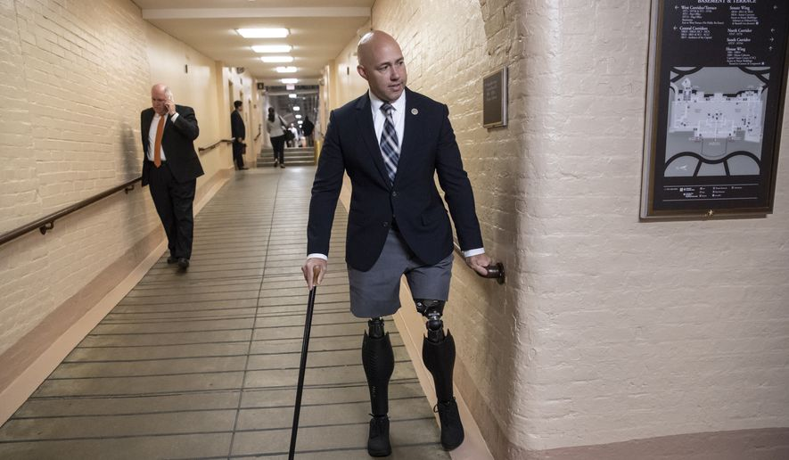 In this photo taken Wednesday, June 20, 2018, Rep. Brian Mast, R-Fla., walks to a meeting with fellow Republicans in the Capitol in Washington. Authorities say a Florida man has been arrested after threatening Rep. Mast and his family over the Trump administration's child-separation immigration policy. (AP Photo/J. Scott Applewhite)