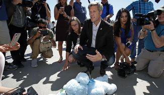 Albuquerque Mayor Tim Keller and his wife Elizabeth leave a teddy bear as a gift for immigrant children that are being held at a facility in Tornillo, Texas, near the Mexican border, Thursday, June 21, 2018.  Mayors from more than a dozen U.S. cities including New York and Los Angeles gathered near the holding facility to call for the immediate reunification of immigrant children with their families.  (AP Photo/Andres Leighton)