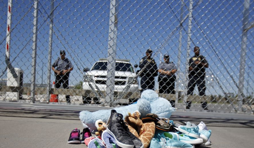 Shoes and a teddy bear, brought by a group of U.S. mayors, are piled up outside a holding facility for immigrant children in Tornillo, Texas, near the Mexican border, Thursday, June 21, 2018.  Mayors from more than a dozen U.S. cities including New York and Los Angeles gathered near the holding facility to call for the immediate reunification of immigrant children with their families.  (AP Photo/Andres Leighton)