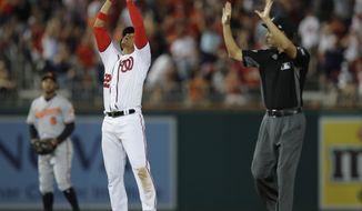 Washington Nationals' Juan Soto (22) gestures as he stands on second base after hitting a two-run double against the Baltimore Orioles during the eighth inning of a baseball game at Nationals Park, Thursday, June 21, 2018, in Washington. Standing at left is Orioles second baseman Jonathan Schoop, and at right is second base umpire Ed Hickox. The Nationals won 4-2. (AP Photo/Carolyn Kaster)