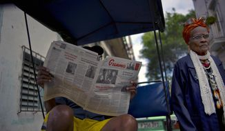 FILE - In this Feb. 3, 2015 file photo, a man reads a copy of the official newspaper of the Central Committee of the Cuban Communist Party, Granma, as a woman walks past, in old Havana. Cuba is slightly loosening controls on its state-run media under its new president. (AP Photo/Ramon Espinosa, File)