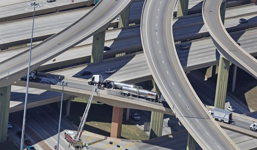 A fuel tanker truck sits overturned atop an elevated exchange along the eastbound ramp of Interstate 635 in Dallas, Thursday, June 21, 2018. The High Five interchange of U.S. Highway 75 and Interstate 635, including all ramps was shut down most of Thursday morning. (Louis DeLuca/The Dallas Morning News via AP)