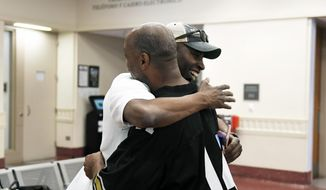 In this  June 14, 2018, photo, Vincent Bowen, left, with Black Lives Matter 5280 hugs Alfred Sisco, right, 56, of Denver, as he is released on bail from the Denver Downtown Detention Center in Denver, Colo. The Denver Justice Project and Black Lives Matter 5280 are bailing out a few individuals as part of a campaign to push bail reform and end the money bail system, especially for low-level crimes. (Joe Amon/The Denver Post via AP)