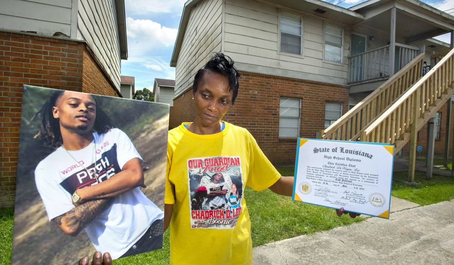 In this June 11, 2018 photo, Denise Lee, the mother of resident Chadrick D. Lee, stands near where he was fatally shot on Nov. 5, 2017, outside his apartment building in Baton Rouge, La. Lee holds a photograph of her son and his diploma from East Feliciana High School. Lee has spent hundreds of hours combing through social media, interrogating her own family members and pleading with potential witnesses, hoping her words will resonate enough for someone somewhere to come forward with information. (Travis Spradling/The Advocate via AP)
