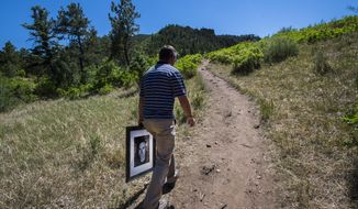 "In this June 1, 2018 photo, Clayton ""Cole"" Cole carries a portrait of his brother, Lee Cole, as he hikes into the Strawberry Hill area of Colorado Springs, Colo., to the spot where his brother posted a Facebook Live video before taking his own life by jumping off a cliff. Lee Cole, 39, was an Army National Guard veteran who was struggling with depression, PTSD, and chronic pain he'd suffered after a training accident before being deployed. His body was found April 2, by a stranger who'd seen the Facebook post and headed out to find him. (Christian Murdock/The Gazette via AP)"