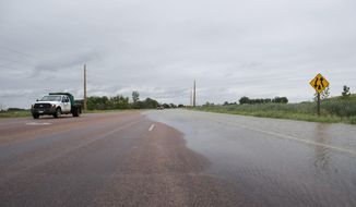 Highway 11, south of 57th Street in north Lincoln County, S.D., is flooded Thursday, June 21, 2018. (Loren Townsley/The Argus Leader via AP)