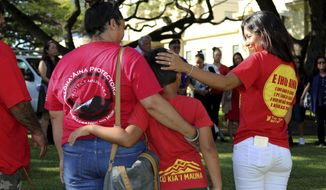 Joanna Pokipala, left, her son Kala Pokipala, center, and Vivian Wong, right, gather with telescope protesters outside the Hawaii Supreme Court building in Honolulu on Thursday, June 22, 2018. Justices are considering an appeal to a decision granting a construction permit for the Thirty Meter Telescope planned for Hawaii's tallest mountain. Protesters say the project will desecrate land that's sacred to Native Hawaiians. (AP Photo/Jennifer Sinco Kelleher)