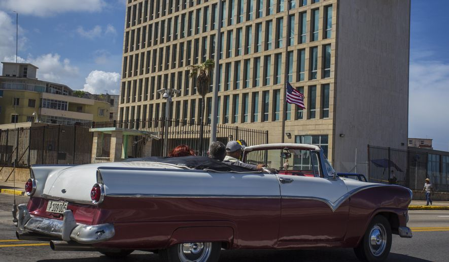 In this Oct. 3, 2017, file photo, tourists ride a classic convertible car on the Malecon beside the United States Embassy in Havana, Cuba. Medical tests have confirmed that one additional U.S. Embassy worker has been affected by mysterious health incidents in Cuba, bringing the total number to 25. That's according to an unclassified notice sent to congressional officials by the State Department. (AP Photo/Desmond Boylan, File)