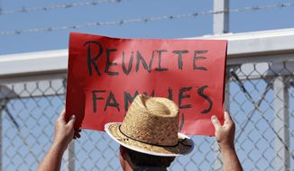 A protester holds a sign outside a closed gate at the Port of Entry facility, Thursday, June 21, 2018, in Fabens, Texas, where tent shelters are being used to house separated family members. President Donald Trump's order ending the policy of separating immigrant families at the border leaves a host of unanswered questions, including what happens to the more than 2,300 children already taken from their parents and where the government will house all the newly detained migrants in a system already bursting at the seams. (AP Photo/Matt York)