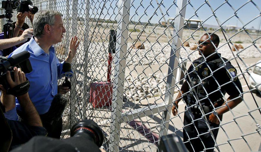 New York City Mayor Bill de Blasio, left, requests entrance to the holding facility for immigrant children in Tornillo, Texas, near the Mexican border, Thursday, June 21, 2018. About 20 mayors from cities across the country are calling for the immediate reunification of immigrant children with their families. (AP Photo/Andres Leighton)