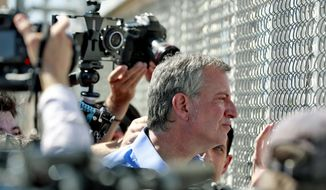 New York City Mayor Bill de Blasio looks through a closed gate at the Port of Entry facility, Thursday, June 21, 2018, in Fabens, Texas, where tent shelters are being used to house separated family members. Mayors from more than a dozen U.S. cities including New York and Los Angeles gathered near the holding facility for immigrant children on Texas' border with Mexico to call for the immediate reunification of immigrant children with their families. (AP Photo/Matt York)