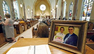 FILE - In this Aug. 29, 2016, file photo, a photograph showing Sisters Margaret Held, left, of the School Sisters of St. Francis, and Paula Merrill, of the Sisters of Charity of Nazareth, sits at the entrance to the Cathedral of St. Peter the Apostle in Jackson, Miss., where a memorial Mass was held fo ther two 68-year-old nuns, who were killed in their Durant home. District Attorney Akillie Malone-Oliver told The Associated Press Tuesday, June 12, 2018, that Robert Earl Sanders of Kosciusko, charged with killing the two nuns will plead guilty, Thursday, June 21, 2018, as part of an agreement that removes the possibility of the death penalty. (AP Photo/Rogelio V. Solis, File)