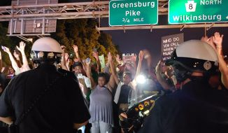 """Protesters chant """"Hands up! Don't shoot!"""" at motorcycle officers near the head of a line of vehicles stuck on Interstate 376 in Pittsburgh on Thursday, June 21, 2018. The highway was shut down by the people protesting the East Pittsburgh police after the June 19 shooting death of Antwon Rose, a 17-year-old boy fatally shot by a police officer in Pennsylvania seconds after he fled a traffic stop. He did not pose a threat to anyone, a lawyer for the family of the teen said. (Andrew Goldstein/Pittsburgh Post-Gazette via AP)"""