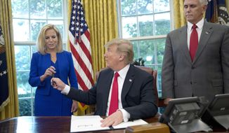 In this June 20, 2018, photo, President Donald Trump gives the pen he used to sign the executive order to end family separations at the border to Homeland Security Secretary Kirstjen Nielsen, left, as Vice President Mike Pence, right, watches in the Oval Office of the White House in Washington. Nielsen has one hard-earned presidential signing pen, receiving hers after Trump used it to sign the executive order. By the time Trump reversed his policy Wednesday, Nielsen had been both yelled at and praised by Trump and pilloried for repeating his falsehoods.  (AP Photo/Pablo Martinez Monsivais)