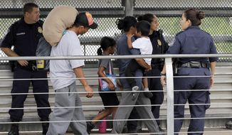 Ever Castillo, left, and his family, immigrants from Honduras, are escorted back across the border by U.S. Customs and Border Patrol agents Thursday, June 21, 2018, in Hildalgo, Texas. The parents were told they would be separated from their children and voluntarily crossed back to Mexico after trying to seek asylum in the United States. (AP Photo/David J. Phillip) **FILE**