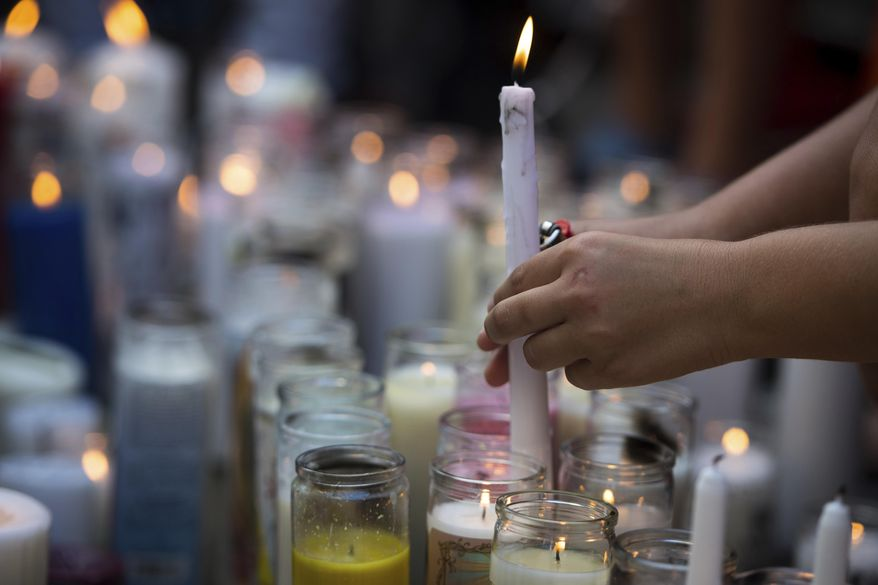 In this Tuesday, June 19, 2018 photo, fans and community members light candles as they gather at a vigil for rap singer XXXTentacion in Deerfield Beach, Fla., near the site where the troubled rapper-singer was killed the day before. The 20-year-old rising star, whose real name is Jahseh Dwayne Onfroy, was shot outside the motorcycle dealership on Monday, June 18, when two armed suspects approached him, authorities said. (Tuesday, June 19, 2018,/South Florida Sun-Sentinel via AP)