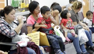 Immigrant women and children wait inside the bus station after they were processed and released by U.S. Customs and Border Protection, Friday, June 22, 2018, in McAllen, Texas. (AP Photo/David J. Phillip)
