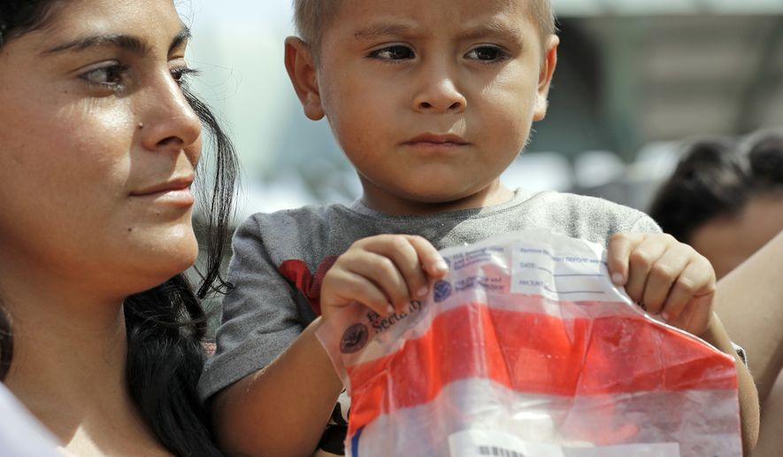 An immigrant child holds bag from Homeland Security as he arrives at the bus station after being processed and released by U.S. Customs and Border Protection, Friday, June 22, 2018, in McAllen, Texas. (AP Photo/David J. Phillip)