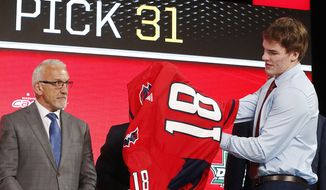 Alexander Alexeyev, right, of Russia, puts on a jersey after being selected by the Washington Capitals during the NHL hockey draft in Dallas, Friday, June 22, 2018. (AP Photo/Michael Ainsworth) ** FILE **