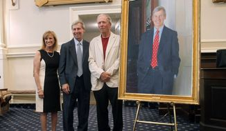 """Former New Hampshire Gov. John Lynch, center poses with his wife, Dr. Susan Lynch, and artist Ralph """"Stoney"""" Jacobs, during the unveiling of his official portrait in Concord, N.H., Friday, June 22, 2018. Lynch, a Democrat, was elected in 2004 and served four terms. (AP Photo/Holly Ramer)"""