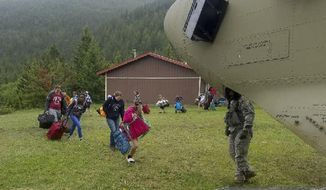 In this photo provided by the Montana Army National Guard, middle school students attending a Bible camp at the Montana Wilderness School of the Bible along the Rocky Mountain Front are guided onto a Chinook helicopter Thursday, June 21, 2018. The campers were flown to Great Falls after flooding earlier this week washed out the road to the camp. (Montana Army National Guard via AP)