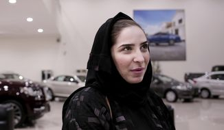In this June 21, 2018 photo, Nour Obeid looks at cars at the Al-Jazirah Ford showroom in Riyadh, Saudi Arabia. This Sunday, Saudi Arabia will lift the world's only ban on women driving and Obeid's husband is encouraging her to get her license and drive. (AP Photo/Nariman El-Mofty)