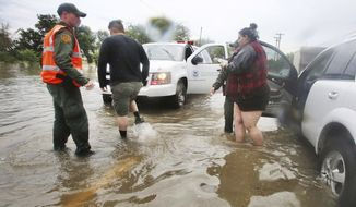 U.S. Border Patrol agents help a stranded motorist on Bryan Road after heavy rains caused water to rise and flood whole neighborhoods, Thursday, June 21, 2018, in Mission, Texas. (Joel Martinez/The Monitor via AP)