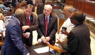 """State Rep. Rob Shadoin, R-Ruston, second from left, speaks with, from left, Reps. Joe Bouie, D-New Orleans; Charles """"Bubba"""" Chaney, R-Rayville; John Bagneris, D-New Orleans; and Jeff Hall, D-Alexandria, on the House floor as sales tax negotiations continued, Friday, June 22, 2018, in Baton Rouge, La. (AP Photo/Melinda Deslatte)"""